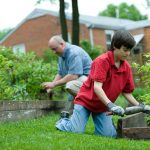 Dad and son working on a home garden