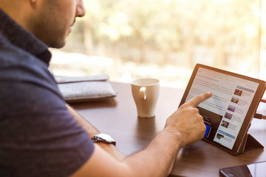 Man searching for real estate agents on a tablet